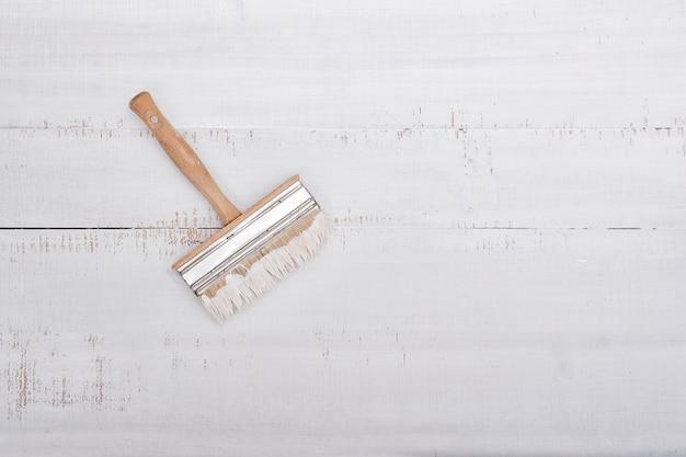 Conceito de renovação de casa. pincel com tinta sobre um fundo branco de madeira gasto com espaço de cópia