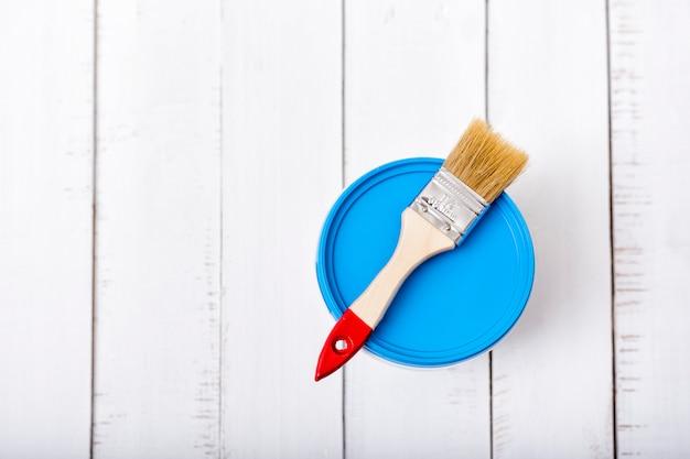 Conceito de renovação de casa. pincel e um balde de tinta em pranchas de madeira surradas brancas.
