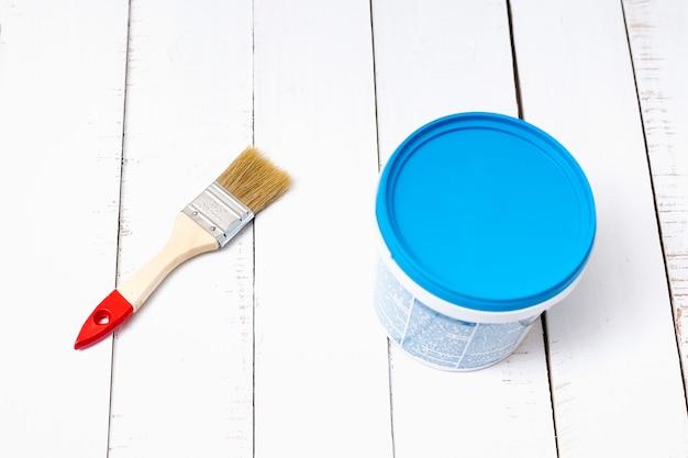Conceito de renovação de casa. pincel e um balde de tinta em um fundo de pranchas de madeira brancas e surradas