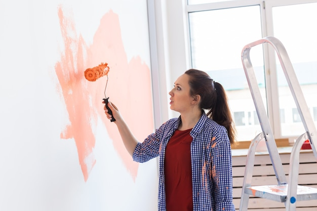 Conceito de renovação, redecoração e reparo - parede de pintura de mulher alegre na nova casa.