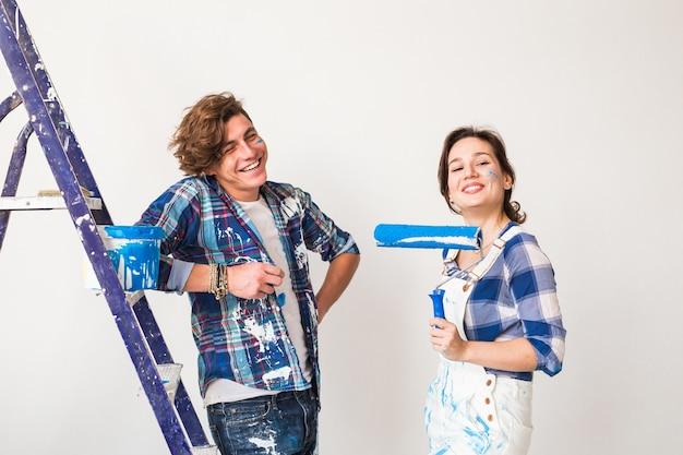 Conceito de renovação, reparação e pessoas - jovem casal que pinta as paredes da sua nova casa.