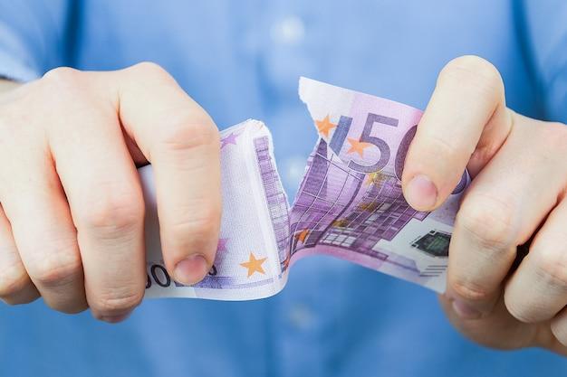 Conceito de renúncia de euro. um homem de camisa azul segura um euro e os rasga.