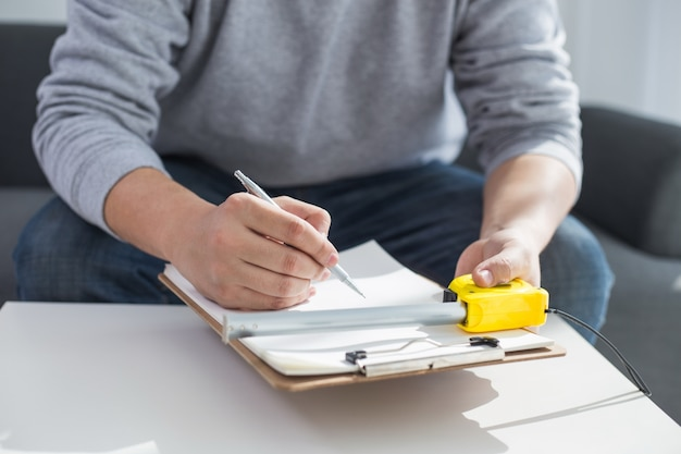 Conceito de reparação, construção e habitação - close up of male hands writing in clipboard