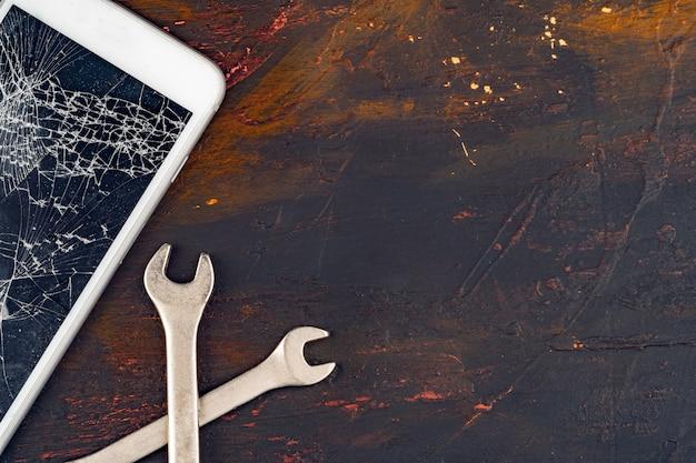 Conceito de reparação de smartphone. exibição danificada de smartphone e ferramentas