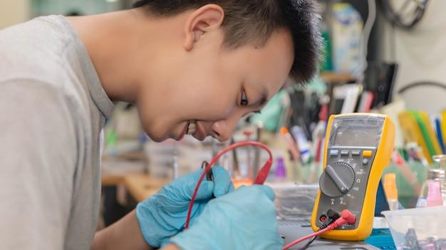 Conceito de reparo do telefone um jovem técnico em eletricidade usando um amperímetro que mede a corrente em um circuito de um dispositivo eletrônico.