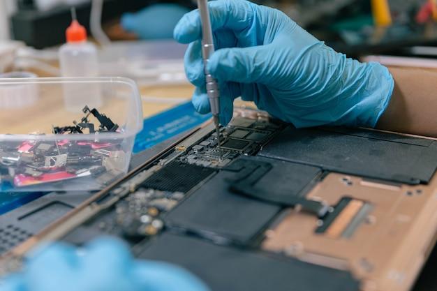 Conceito de reparo do telefone um jovem técnico em eletricidade usando uma chave de fenda para prender as peças de um dispositivo eletrônico.