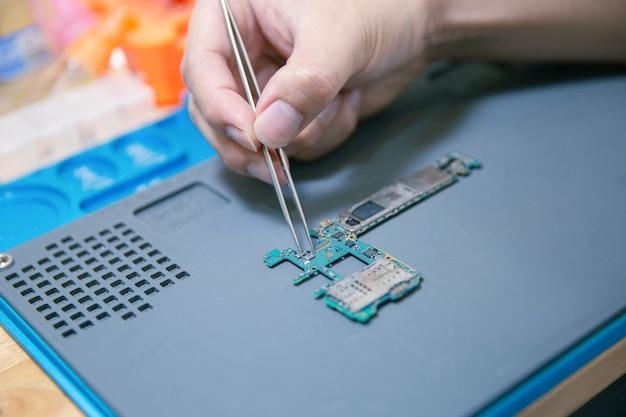 Conceito de reparo do telefone uma mão nua segurando uma pinça segurando uma pequena parte de uma placa de circuito com cuidado e precisão na mesa de madeira.