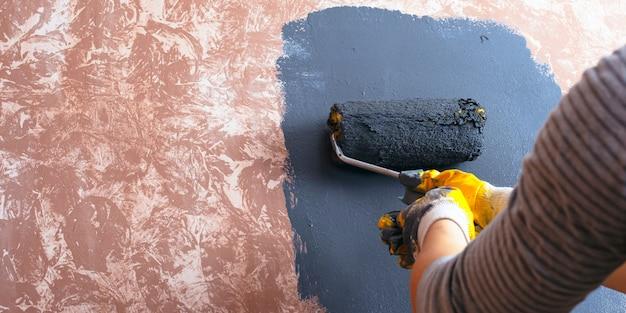 Conceito de reparo em casa. garota pinta uma tinta de parede.