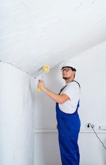 Conceito de reparo, melhoria home e renovação. jovem de macacão azul e capacete branco pintando parede