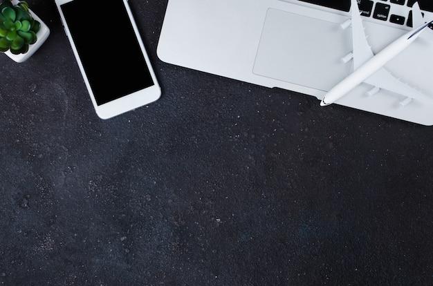 Conceito de reserva de viagens. modelo de laptop, smartphone e avião em fundo escuro.
