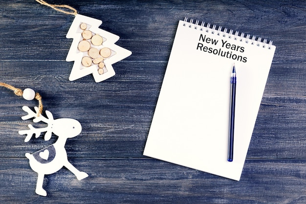 Conceito de resoluções de ano novo. caderno com caneta decorada com enfeites de natal.