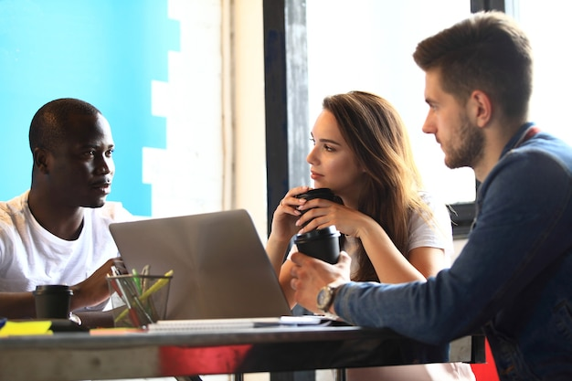 Conceito de reunião de brainstorming de trabalho em equipe de diversidade de startups. colegas de trabalho da equipe de negócios compartilhando documento de relatório da economia mundial