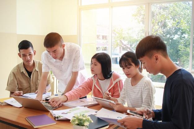 Conceito de reunião de equipe de trabalho de co: nova geração asiática negócios trabalhando juntos a estudar