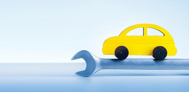 Conceito de revisão, reparação e manutenção automóvel. carro de brinquedo amarelo com a chave inglesa sobre fundo azul com espaço de cópia.