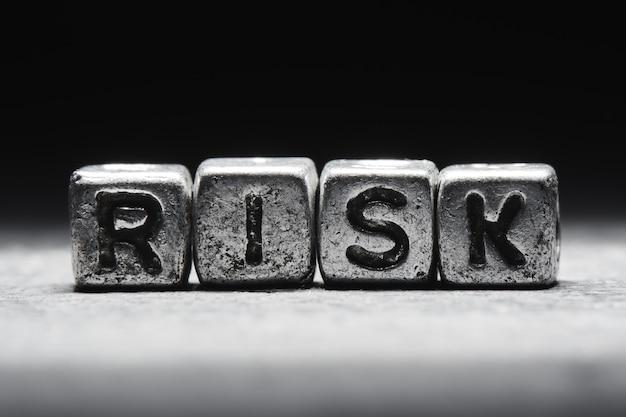 Conceito de risco. a inscrição em cubos 3d de metal isolados em um fundo preto, estilo grunge