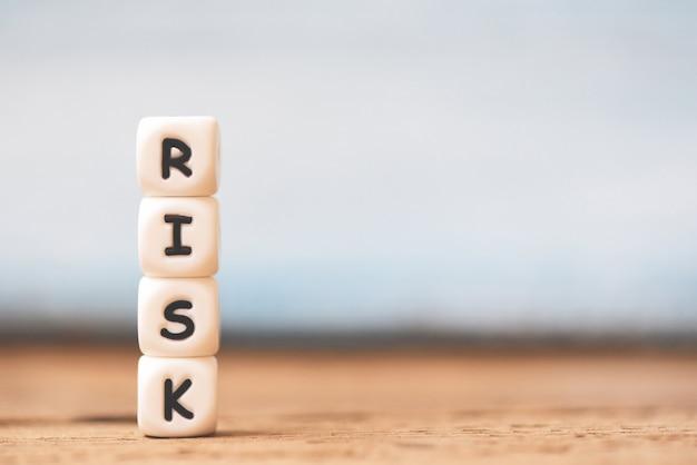 Conceito de risco com risco de bloco empilhado no fundo da mesa de madeira