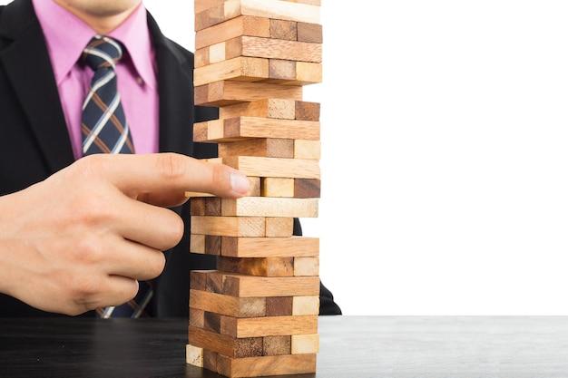 Conceito de risco do negócio com jogo de madeira jenga. homem de negócios gerencia sua estratégia.