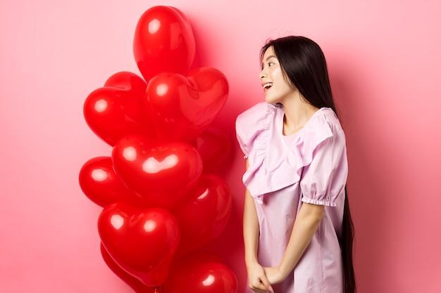 Conceito de romance e amor. menina asiática romântica olhando com carinho e simpatia para o espaço vazio, em pé perto de balões de corações vermelhos do amante, fundo rosa.