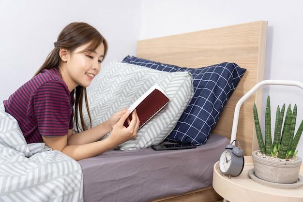 Conceito de rotina diária no quarto, uma garota deitada na cama com o livro nas mãos pacificamente.