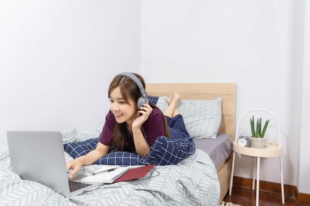 Conceito de rotina diária: uma adolescente ouvindo suas canções favoritas na cama minúscula de seu próprio quarto.