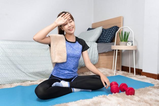 Conceito de rotina diária, uma jovem sentada no tapete, suando depois de fazer o treino no quarto dela.