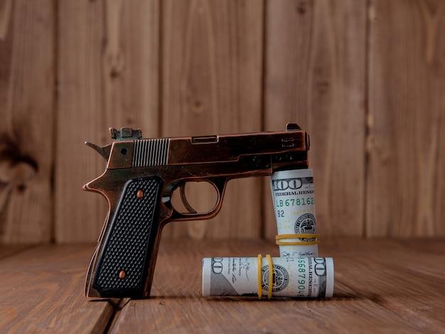 Conceito de roubo. arma com dinheiro na parede de madeira.