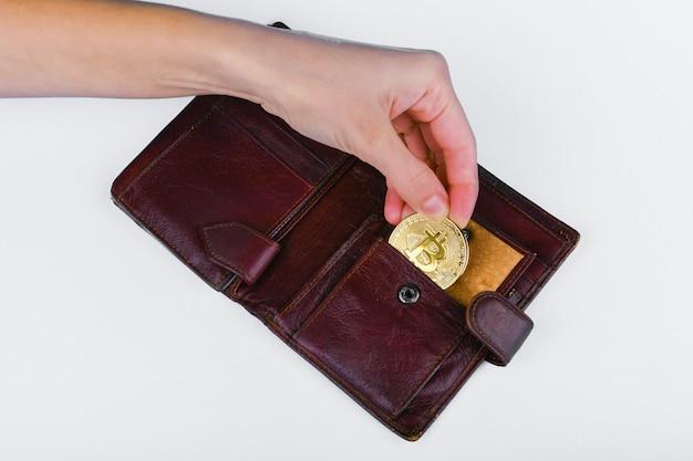 Conceito de roubo de bitcoin. a mão rouba bitcoin de uma carteira.