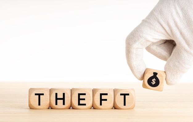 Conceito de roubo. mão, escolhendo um bloco de madeira com ícone de saco de dinheiro e texto em dados de madeira. copie o espaço.