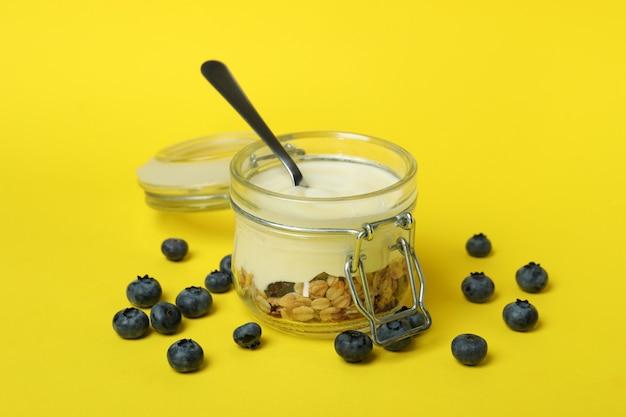 Conceito de saboroso café da manhã com iogurte em fundo amarelo