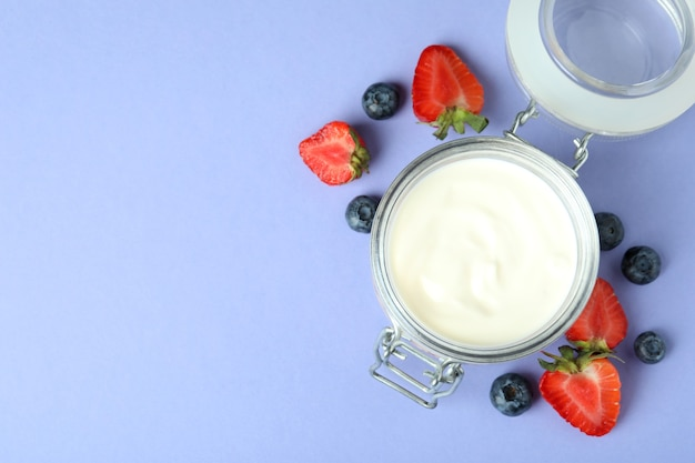 Conceito de saboroso café da manhã com iogurte em fundo violeta