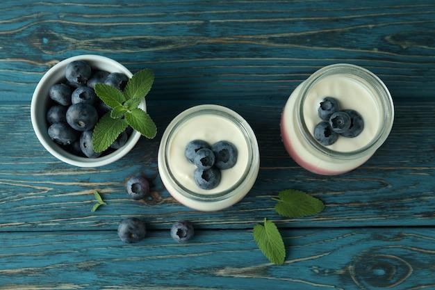 Conceito de saboroso café da manhã com iogurte na mesa de madeira