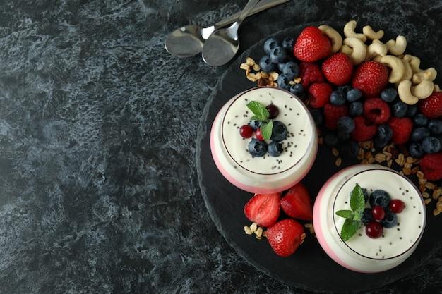 Conceito de saboroso café da manhã com iogurte na mesa esfumada preta
