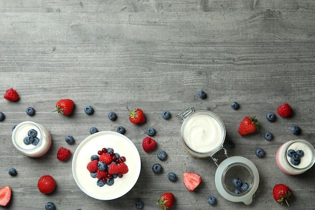 Conceito de saboroso café da manhã com iogurte na mesa texturizada cinza