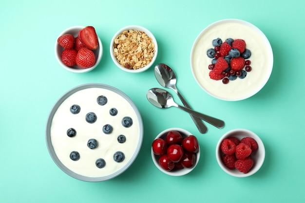 Conceito de saboroso café da manhã com iogurte no fundo de hortelã