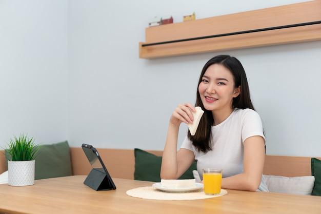 Conceito de sala de estar, um adulto do sexo feminino desfrutando de comer sanduíches e suco de laranja, assistindo a mídia online no intervalo do trabalho.