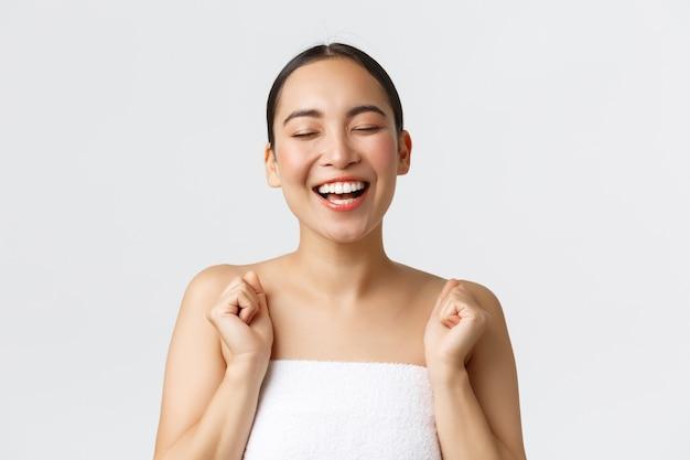 Conceito de salão de beleza, cosmetologia e spa. close-up de feliz linda mulher asiática na toalha de banho feche os olhos despreocupados e rindo de alegria, anúncio de clínica de beleza, massagem terapêutica, depilação.
