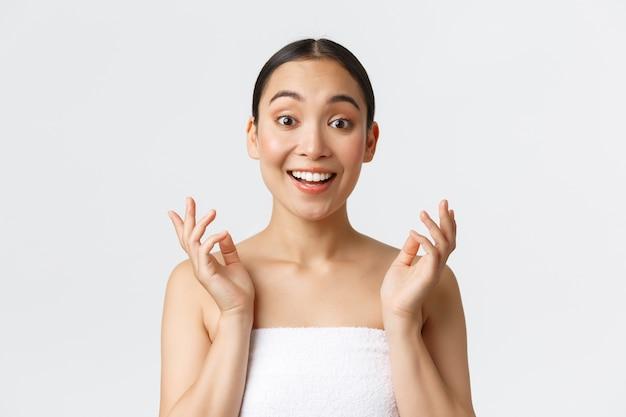Conceito de salão de beleza, cosmetologia e spa. surpresa e feliz linda garota asiática na toalha reage para limpar a pele perfeita após a terapia de pele ou massagem, parece impressionada e satisfeita.