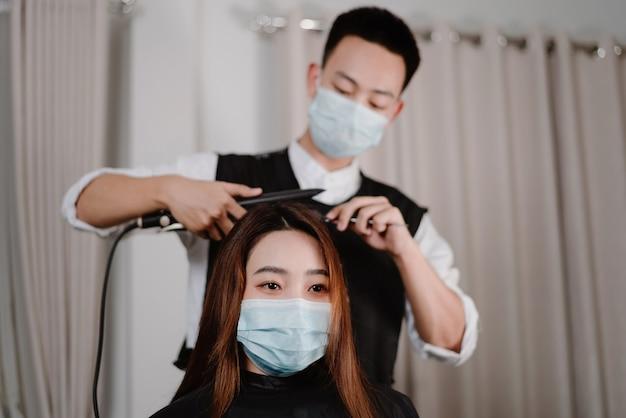 Conceito de salão de cabeleireiro tanto o cabeleireiro masculino quanto o cliente feminino usando máscaras protetoras durante o processo de corte de cabelo.
