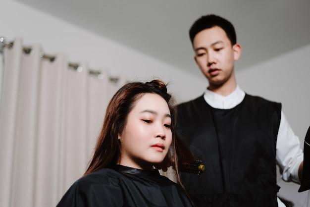 Conceito de salão de cabeleireiro um cabeleireiro masculino usando um secador de cabelo