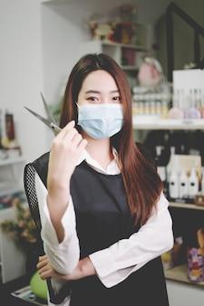 Conceito de salão de cabeleireiro, uma bonita cabeleireira posando com tesouras em uma mão em seu salão de cabeleireiro, rodeado por equipamentos e produtos de cuidado de cabelo.