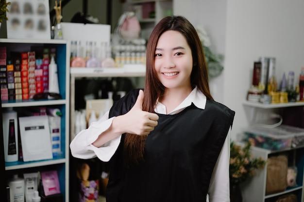 Conceito de salão de cabeleireiro: uma linda cabeleireira posando em seu salão de cabeleireiro cercada por produtos e equipamentos para cuidados com os cabelos