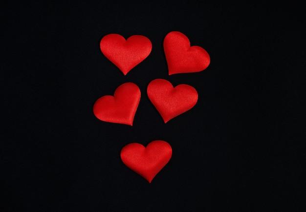 Conceito de são valentim. a vista superior dos corações vermelhos espalhou-se sobre um fundo preto. fronteira, cópia espaço, celebração, feriado