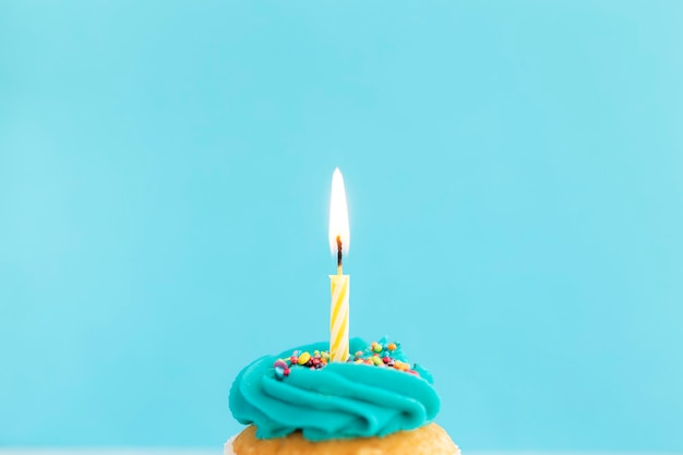 Conceito de saudações de aniversário. vela acesa em um bolinho ou bolinho.