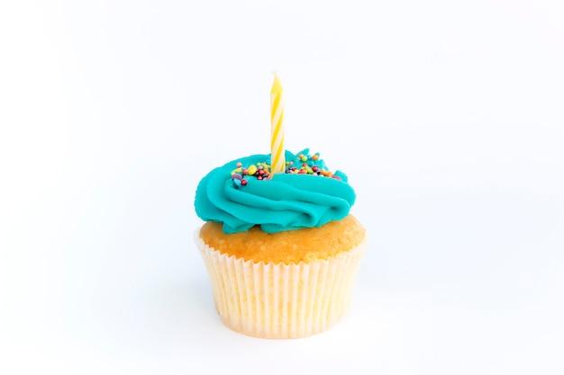Conceito de saudações de aniversário. vela amarela em um bolinho ou bolinho.