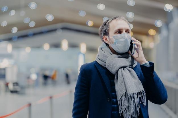 Conceito de saúde, comunicação e epidemia. o homem sério usa máscara médica protetora, se preocupa com a segurança para não pegar o coronavírus, entra no shopping, conversa por telefone celular. proteção antivírus