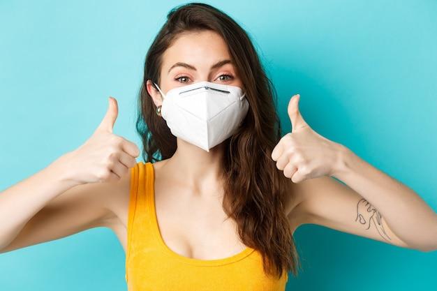 Conceito de saúde covid e bloqueio fechar o retrato de uma mulher alegre na máscara facial mostrando os polegares para cima ...