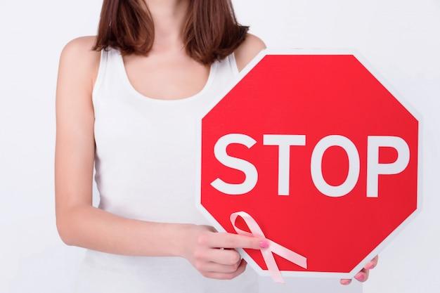Conceito de saúde de doenças oncológicas. menina mulher adulto feminino vestindo blusa branca, segurando o sinal vermelho com fita rosa como símbolo do câncer de mama