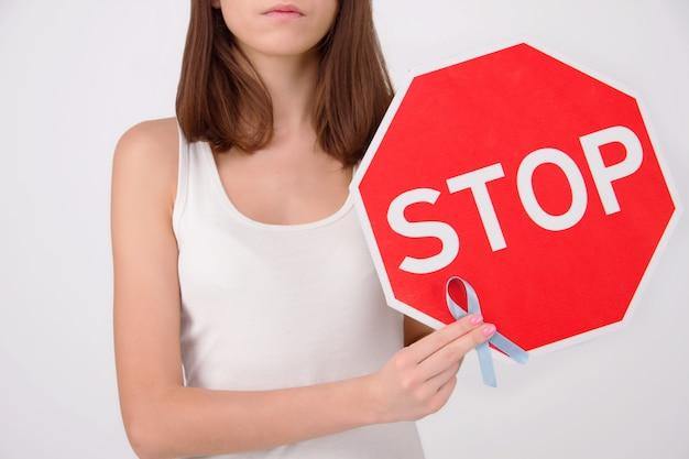 Conceito de saúde de doenças oncológicas. menina / mulher / fêmea / adulto que veste a parte superior branca que guarda o sinal vermelho da parada com fita azul como símbolo do câncer de próstata.