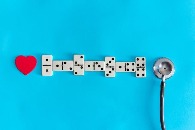 Conceito de saúde do coração. eletrocardiograma com dominó. copie o espaço.