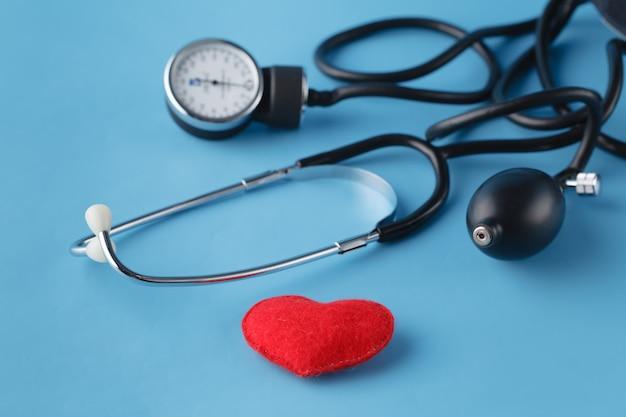 Conceito de saúde do coração, tonômetro e coração de brinquedo em azul